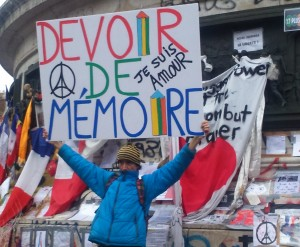 """Un homme brandissant une pancarte """"Devoir de mémoire"""""""