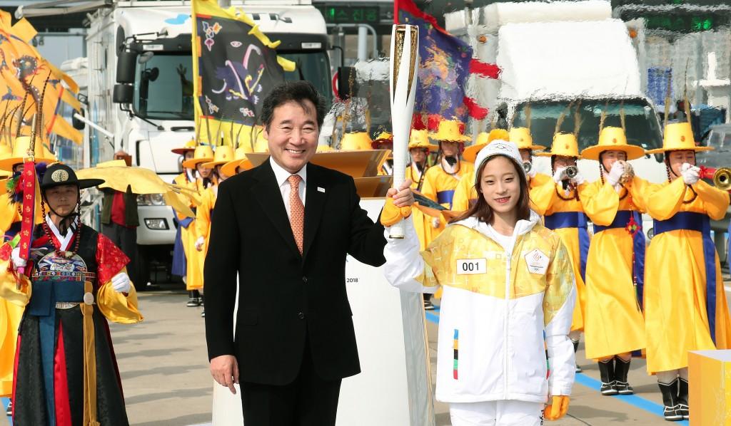 Le ministre de la Culture, du Sport et du Tourisme Do Jong-hwan tient la flamme olympique accompagné de You Young, plus jeune championne nationale de patinage artistique.Auteur : Jeon So-hyang / korea.net / Korean Culture and Information Service (licence CC)